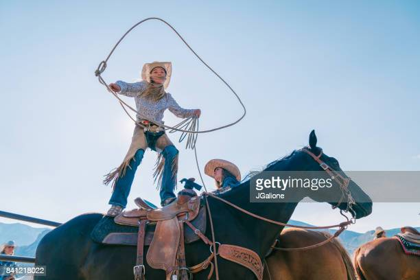 Young cowgirl standing on her horse and swinging her lasso