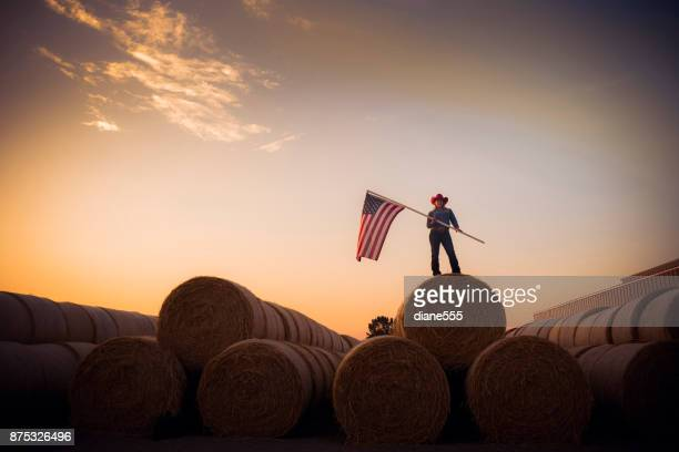 young cowgirl stands on top of a huge pile of hay bales at sunset holding the american flag - patriotic stock pictures, royalty-free photos & images