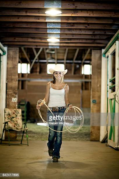 Young cowgirl walking in a barn.