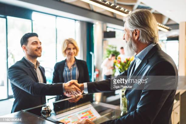 young coworkers checking in a hotel on a business trip - guest stock pictures, royalty-free photos & images