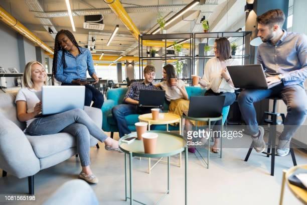 jovens colegas de trabalho no escritório moderno - roupa descontraída - fotografias e filmes do acervo