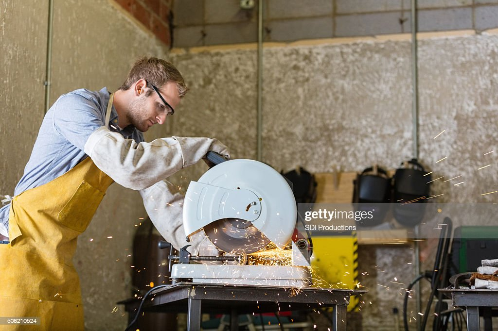 Young craftsman working with saw in professional metal shop : Stock Photo