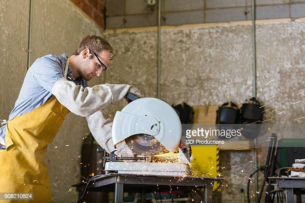 Young craftsman working with saw in professional metal shop