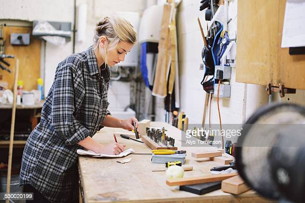 Young craftswoman making notes at workbench in pipe organ workshop