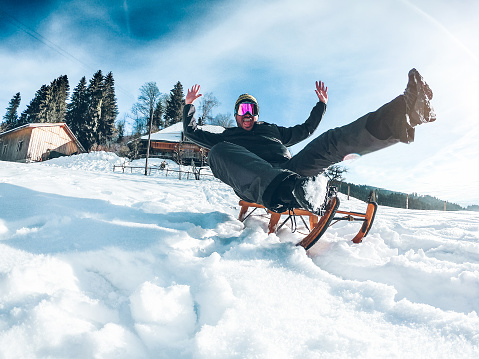 Young crazy man having fun with wood vintage sledding on snow mountain landscape - Happy guy enjoy winter vacation - Holiday concept - Focus on his face 1098314828