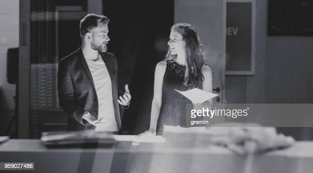 em pé de casal de jovens criativos de negócios sobre mesa iluminada - debate - fotografias e filmes do acervo