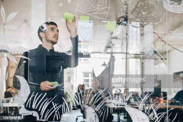young creative businessman sticking adhesive note on patterned glass in office - geschäftsgründung stock-fotos und bilder