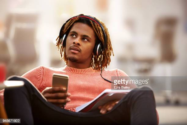 Young creative man listening to headphones in industrial office space.
