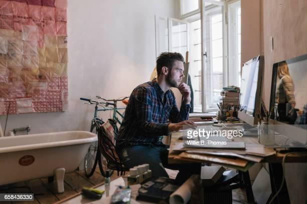 young creative man working on computer - kreativer beruf stock-fotos und bilder