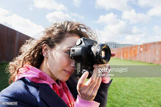 Young creative taking pictures with digital camera