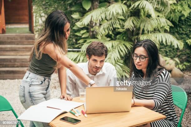 Jungen kreativen Team mit Laptop vor Büro