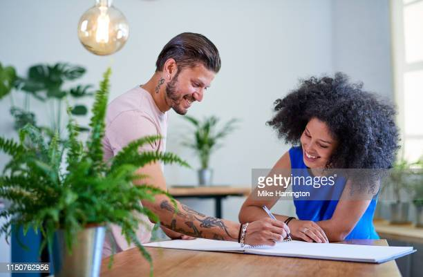 young creative team working in contemporary sustainable creative office environment - sleeveless dress stock pictures, royalty-free photos & images