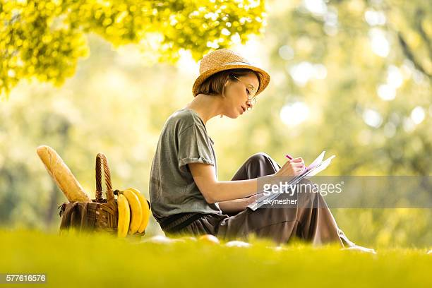 Young creative woman sketching on the paper at picnic.