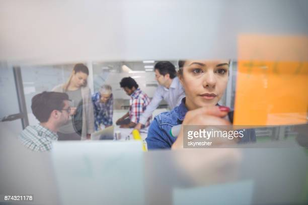 Young creative woman writing business strategy on adhesive note in the office.