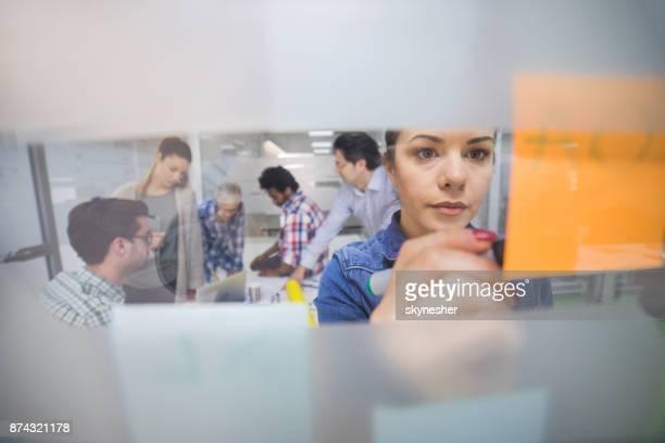 Jonge creatieve vrouw schrijven bedrijfsstrategie op zelfklevende noot in het kantoor.