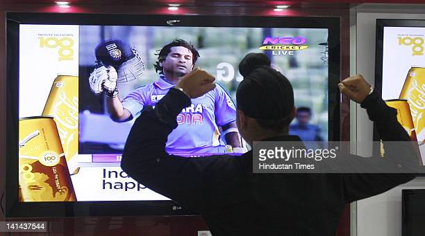 A young cricket fan celebrates as he watches a tv screen after Sachin Teldulkar of India scored his 100th century in international cricket on March...
