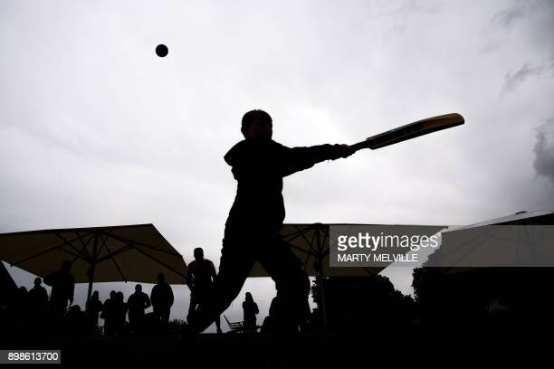 TOPSHOT Young cricket fans play a pickup game of cricket as rain causes a delay in play during the third oneday international cricket match between...