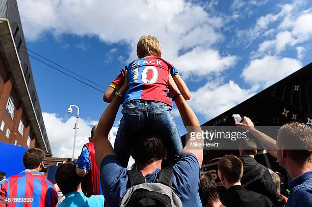 A young Crystal Palace fan is lifted by his father prior to the Barclays Premier League match between Crystal Palace and Manchester City at Selhurst...