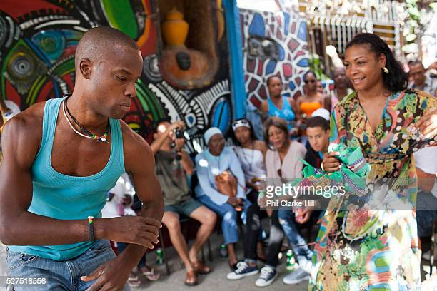 Young Cuban man and woman wearing a colourful dress dancing Rumba Callejon de Hamel a street art project in old Havana which has a Rumba show on a...