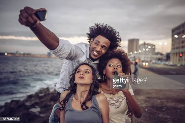 young cuban people taking selfie with mobile at Malecon in Havanna
