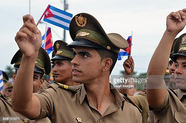 CONTENT] Young Cuban soldiers wave flags at the May Day parade in Plaza de la Revolucion Havana Cuba As they march through the square they turn to...