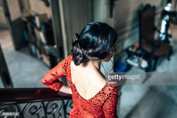 young cuban woman in red dress going down stairs in old house
