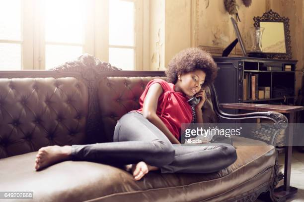 young cuban woman on sofa with telephone