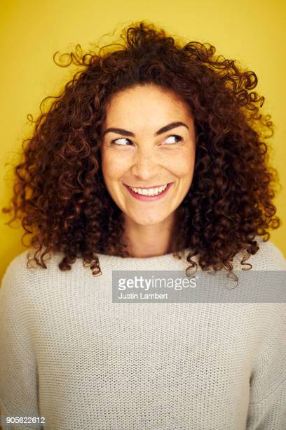 young curly haired woman looking off camera with a cheeky big smile - vertikal stock-fotos und bilder