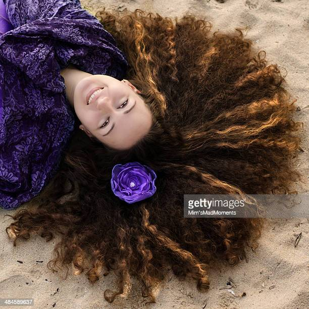 Young curly woman with purple flower