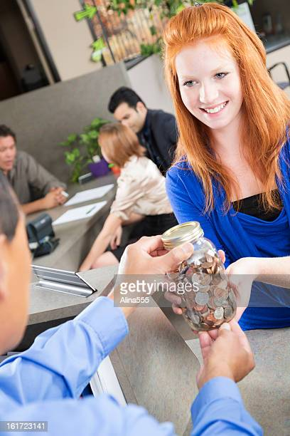young customer at the bank giving coins to teller - alina stock pictures, royalty-free photos & images