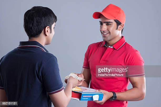 Young customer paying pizza delivery man over gray background