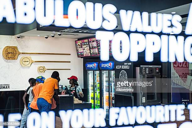 Young customers queue to order food at the service desk inside a Pizza Hut store operated by Yum Brands Inc in the Soweto district of Johannesburg...