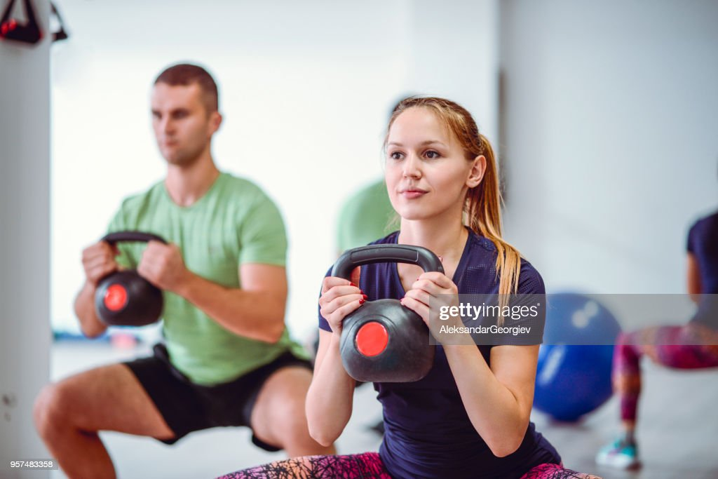 Young Cute Couple Doing Squats With Kettle Bell Weight In The Gym