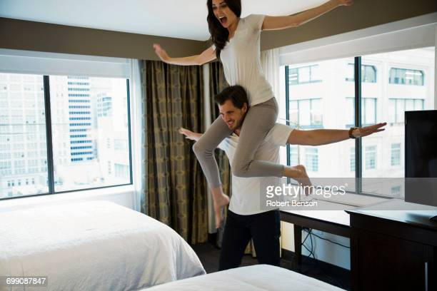 A young cute couple makes fun in a Dallas hotel room.