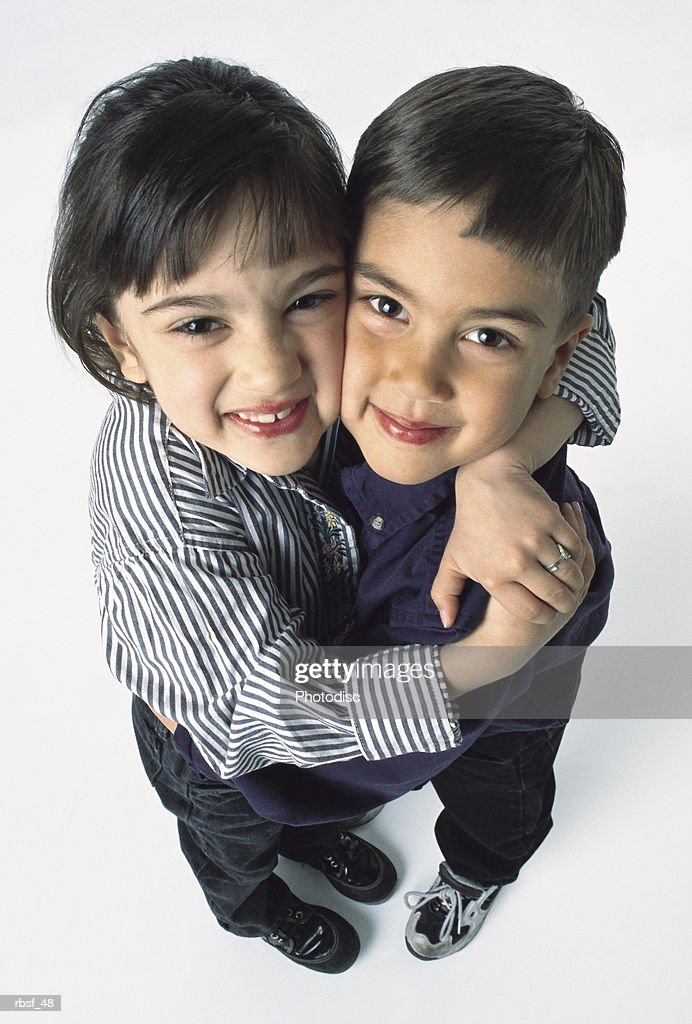 young cute ethnic siblings hug each other and smile : Stockfoto