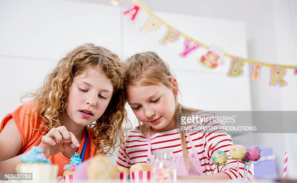 Young cute girls decorating cup cakes