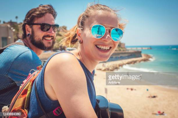 young cute man and woman happy to reach the sea - tel aviv stock pictures, royalty-free photos & images
