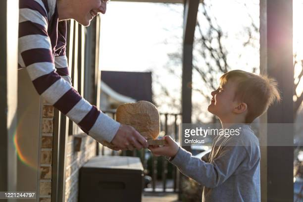young cute redhead kid bringing homemade bread to neighbor's door - stay at home order stock pictures, royalty-free photos & images