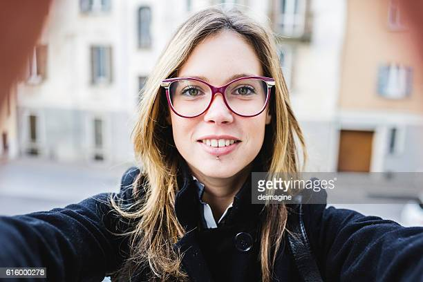 Young cute woman with eyeglasses take a selfie.