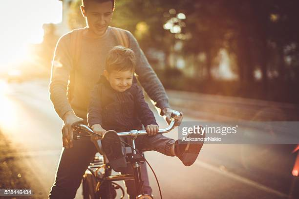 young cyclist and his father - city life stock pictures, royalty-free photos & images