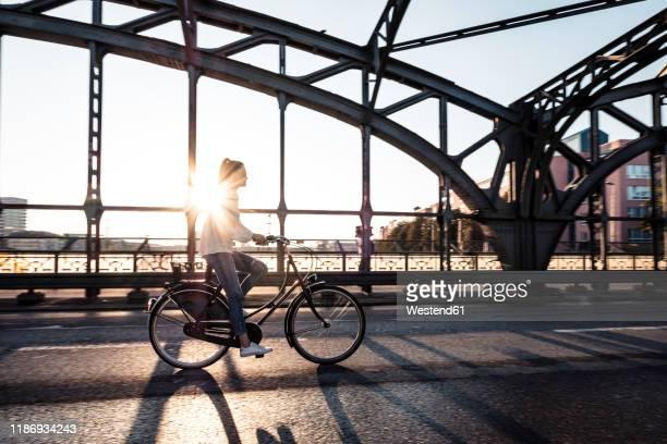 young cyclist on a bridge at sunset - münchen stock-fotos und bilder