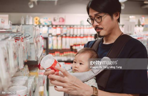 Young dad carrying his baby in a baby carrier shopping for baby products.