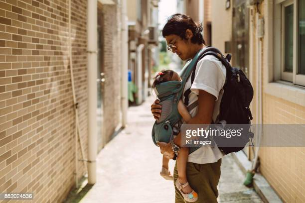 Young dad carrying sleeping baby in a baby carrier.
