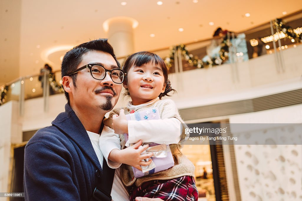 Young dad holding daughter joyfully in mall : Stock Photo