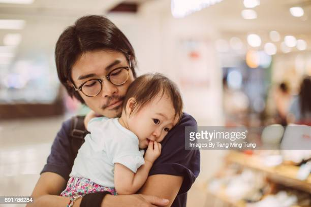 Young dad holding little baby in his arms in shopping mall