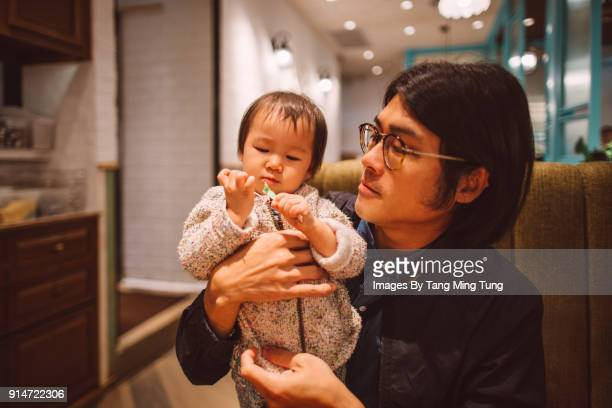 Young dad hugging his baby in a restaurant