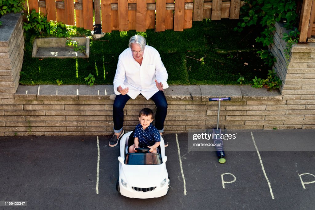 Young dad of 50+ playing with son in driveway : Stock Photo