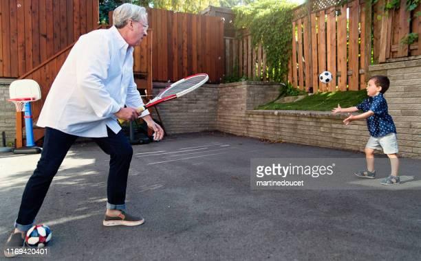 """joven papá de 50+ jugando con su hijo en la entrada - """"martine doucet"""" or martinedoucet fotografías e imágenes de stock"""