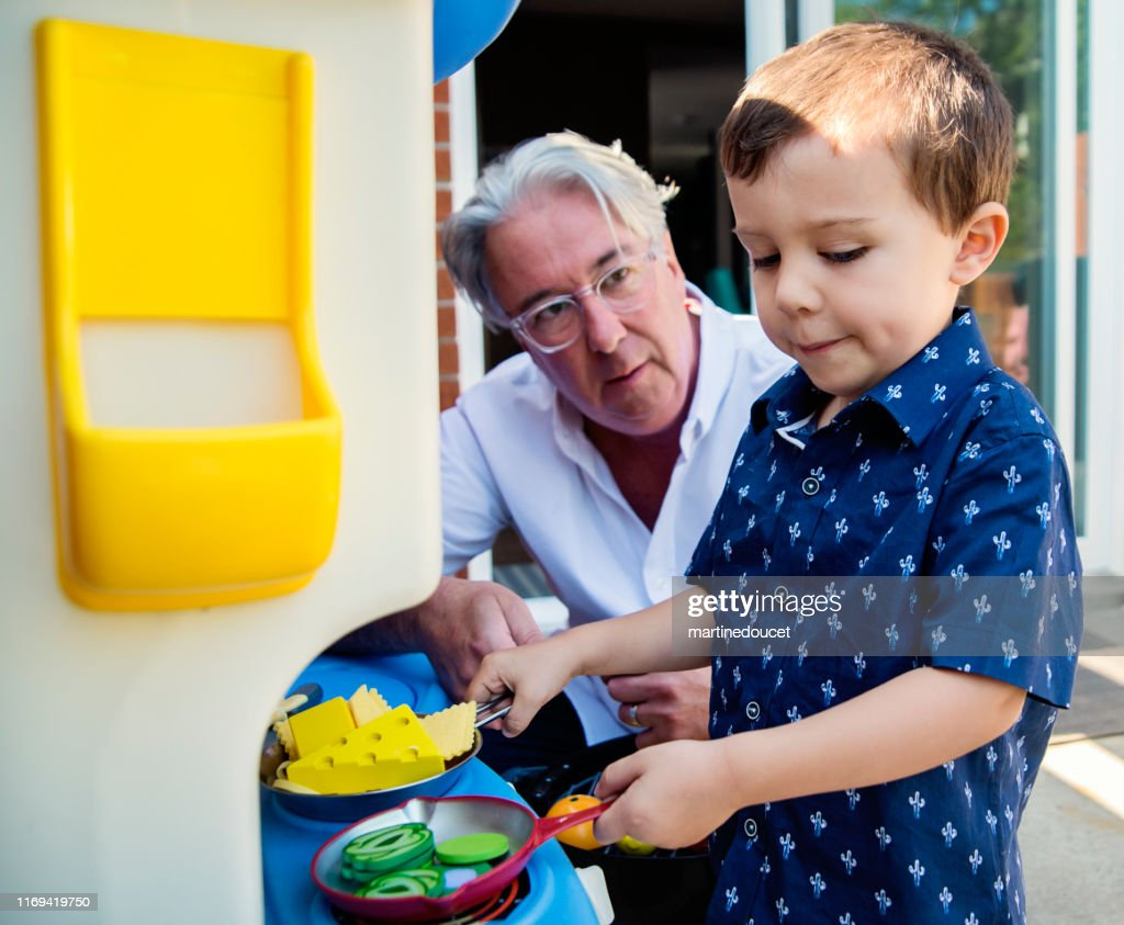 Young dad of 50+ playing with son on home patio : Stock Photo