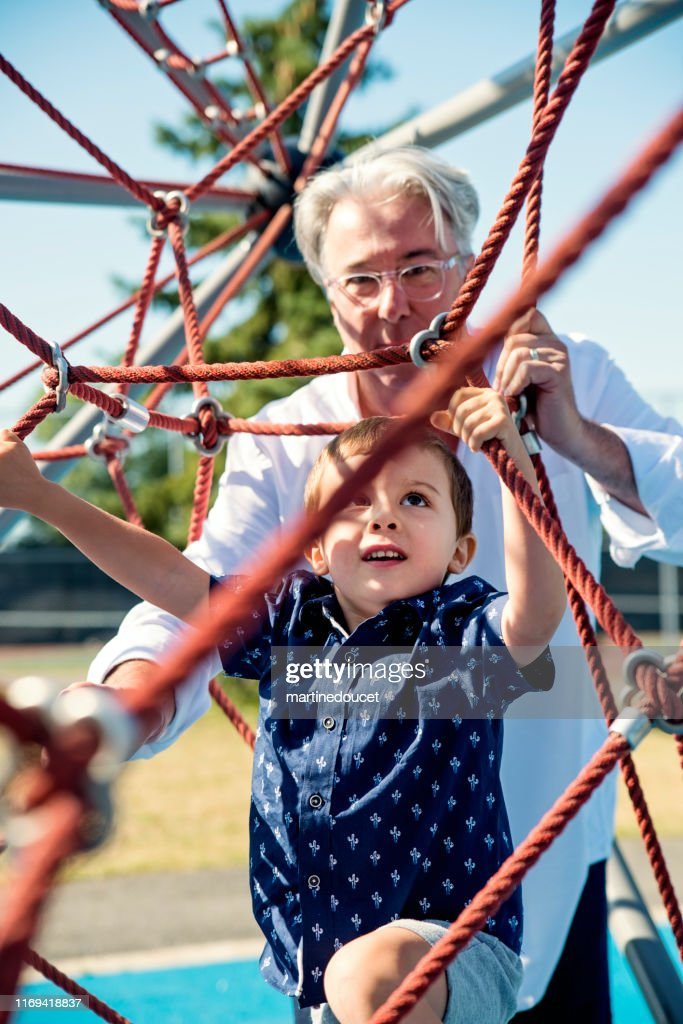 Young dad of 50+ playing with son on playground : Stock Photo